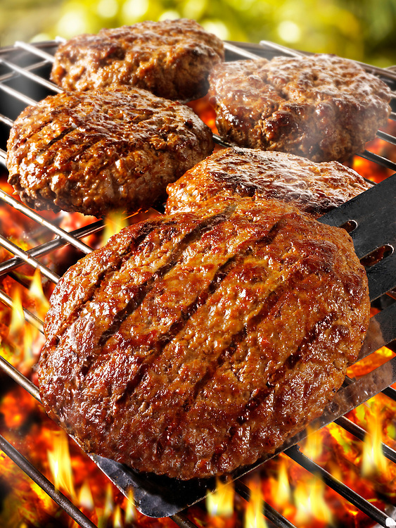BBQ beef burgers being cooked on a bbq grill. Funky Stock library burger images of bbq food.