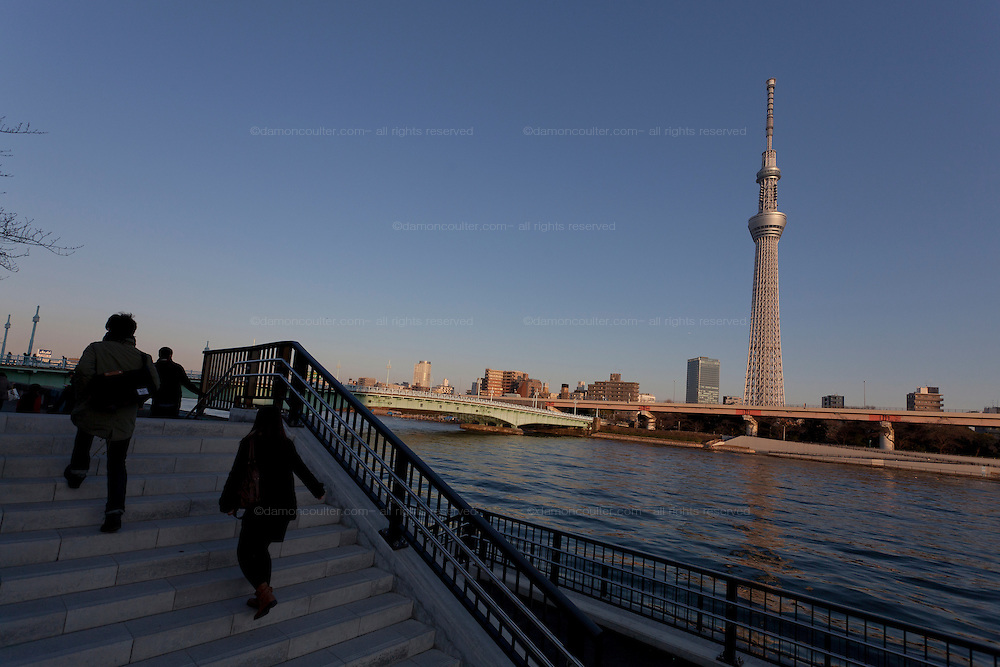 Tourists look at Tokyo Skytree from the steps of a small riverside park in Asakusa, Tokyo, Japan Sunday February 10th 2013