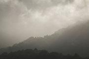 Hills slope with clouds rolling over and a bit of sunlight shining through, The Southern Circuit, Stewart Island / Rakiura, New Zealand Ⓒ Davis Ulands | davisulands.com