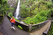 An athletic young woman trail running at Multnomah Falls near Portland, Oregon.  Multnomah falls, located east of Troutdale, Oregon is a popular tourist attraction off of Interstate 84.  The falls drop a total of 620 feet into the Columbia River Gorge making it the third tallest year round waterfall in the United States. (Model Released)