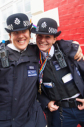 London, June 28th 2014. Two police officers pose for a picture as thousands of London's LGBT community and their supporters throw a vast party in Soho.