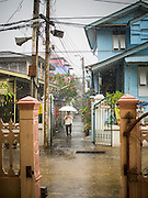 15 FEBRUARY 2015 - BANGKOK, THAILAND: A woman walks through the rain to Sunday mass at Santa Cruz Catholic Church in the Kudeejeen neighborhood in Bangkok. Santa Cruz church was established in 1770  and is one of the oldest and most historic Catholic churches in Thailand. The church was originally built by Portuguese soldiers allied with King Taksin the Great. Taksin authorized the church as a thanks to the Portuguese who assisted the Siamese during the war with Burma. Most of the Catholics in the neighborhood trace their family roots to the original Portuguese soldiers who married Siamese (Thai) women. There are about 300,000 Catholics in Thailand in about 430 Catholic parishes and about 660 Catholic priests in Thailand. Thais are tolerant of other religions and although Thailand is officially Buddhist, Catholics are allowed to freely practice and people who convert to Catholicism are not discriminated against.      PHOTO BY JACK KURTZ