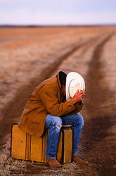 cowboy with his head down sitting on an old suitcase on a dirt road in the middle of nowhere