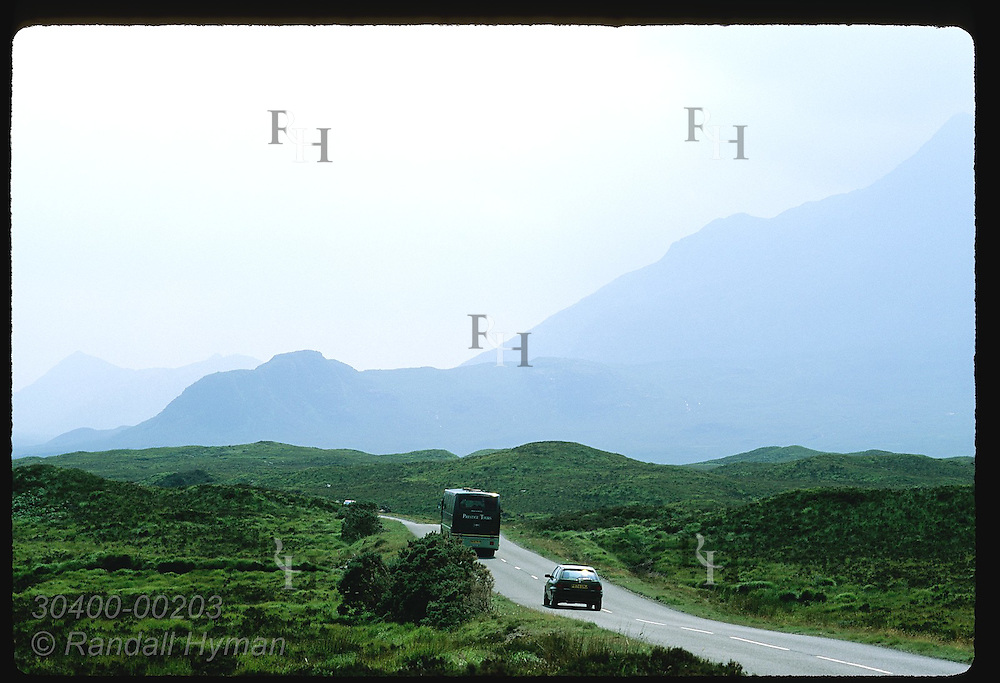 Car and bus speed along highway toward distant mountains on a misty July day; Isle of Skye. Scotland