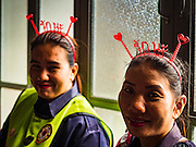 "14 FEBRUARY 2017 - BANGKOK, THAILAND: Cleaning ladies, wearing Valentine's Day headbands waits to start cleaning up after a mass wedding in the Bang Rak district in Bangkok. Bang Rak is a popular neighborhood for weddings in Bangkok because it translates as ""Village of Love."" (Bang translates as village, Rak translates as love.) Hundreds of couples get married in the district on Valentine's Day, which, despite its Catholic origins, is widely celebrated in Thailand.      PHOTO BY JACK KURTZ"