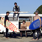 Mike Kalish ( black Xcel wetsuit), twin brother  Charlie Kalish (brown wetsuit), Joe Turpel (red and yellow board,) Aaron Gilliam (wool hat) pose in front Gilliam's VW van at a beach north of Santa Barbara, CA. Model released.
