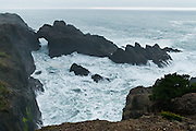 Drive to Indian Sands along Samuel H. Boardman State Scenic Corridor on US Route 101 and walk the Oregon Coast Trail to see the Pacific Ocean crashing on cliffs and through a sea arch, in Curry County, Oregon, USA.