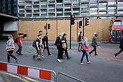 Pedestrians cross a road junction near Tottenham Court Road in central London.