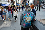 Young woman wearing a denim jacket with a picture of cultural icon Frida Kahlo printed on the back on 14th July 2019 in London, England, United Kingdom. Frida Kahlo was a Mexican painter known for her many portraits, self-portraits, and works inspired by the nature and artifacts of Mexico. Inspired by the countrys popular culture, she employed a naive folk art style.