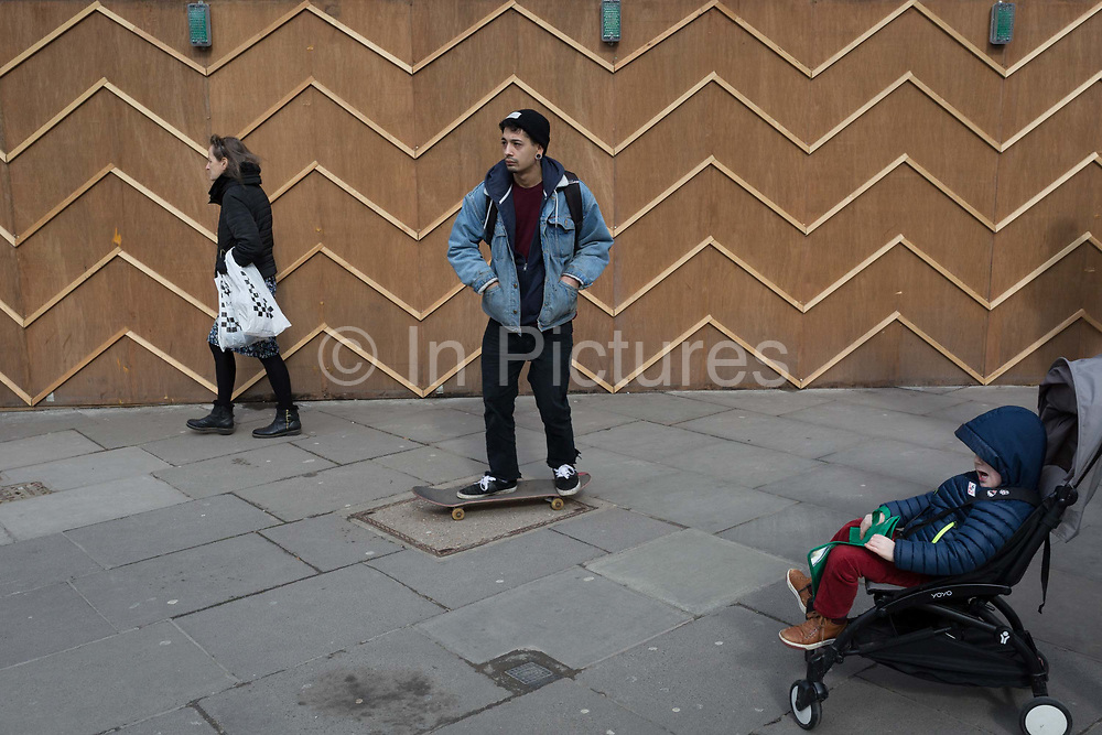 A young man on a skateboard passes the zigzag battons of a construction hoarding at Notting Hill, on 13th March 2018, in London, England.
