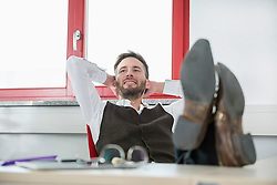 Young man office desk relaxing feet up lazy