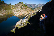 Liana Welty, illuminated against dark shadows, stops to enjoy the views along the trail to Gothic Basin, Mount Baker-Snoqualmie National Forest, Washington.