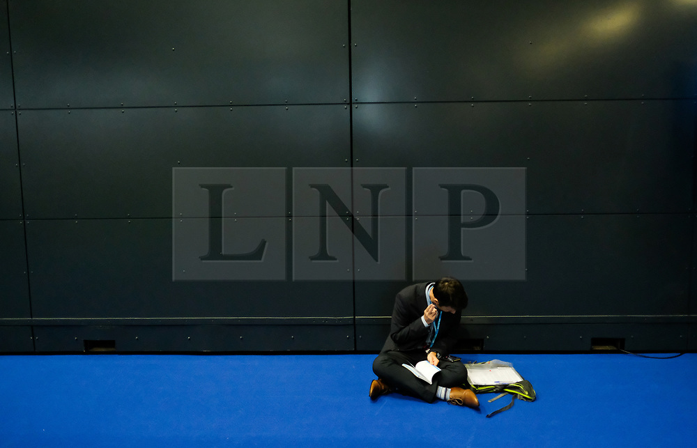 © Licensed to London News Pictures. <br /> 01/10/2017 <br /> Manchester, UK.  <br /> <br /> A man sits on the floor talking on his phone during the Conservative party Conference held in the Manchester Central Convention Complex.<br /> <br /> The conference will offer a schedule of speeches, receptions and fringe events giving a chance for party members and the public to learn about party ideas and policies for the year ahead.<br /> <br /> Photo credit: Ian Forsyth/LNP
