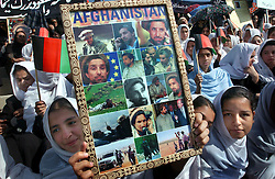 KABUL,AFGHANISTAN - SEPT. 9: An Afghan girl holds a photos of Ahmad Shah Massoud during a ceremony in Kabul Sports Stadium, September 9, 2002  to comemerate the one-year anniversary of his death. (Photo by Ami Vitale/Getty Images)