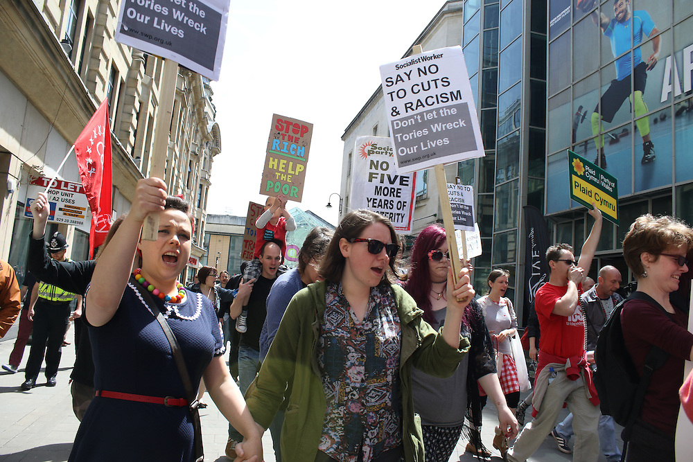 Protesters march through Cardiff city centre during a protest against proposed cuts to public services and benefits