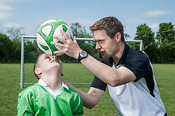Soccer coach practicing with young player