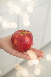 Close-up of red apple on woman's palm, Munich, Bavaria, Germany