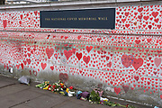 Red hearts painted in memory of people who have died of Covid-19 during the coronavirus pandemic at the National Covid Memorial Wall on 13th April 2021 in London, United Kingdom. The wall is  a place for people to come to reflect or to write messages or the names of lost loved ones. The wall represents a tribute to the approximately 150,000 British victims pandemic.
