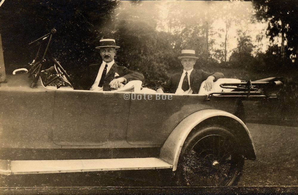 Old fading photograph of father and son in there car.