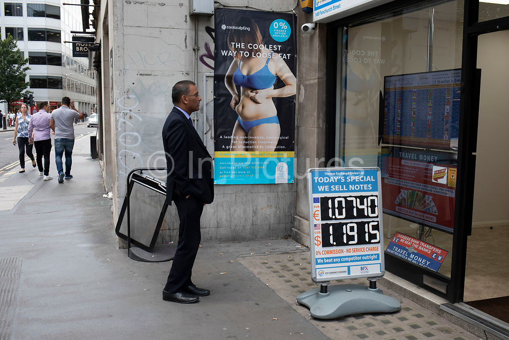 Man looking at a screen showing the various monetary exchange rates for the countries of the World as he stands beside a poster advertising weight loss in the City of London, England, United Kingdom.