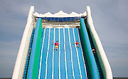Children playing on giant inflated slide seaside attraction, Great Yarmouth, Norfolk, England