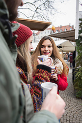 Friends with cup of mulled wine at Christmas market