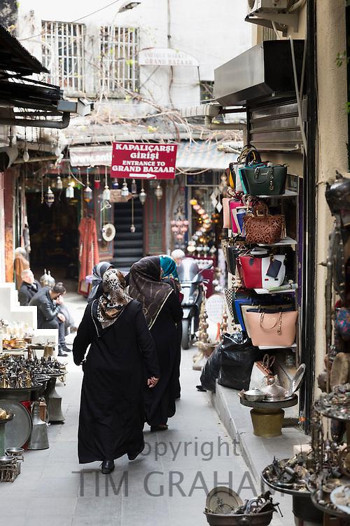 Muslim women wearing traditional robes veils shopping in The Grand Bazaar, Kapalicarsi, great market, Beyazi, Istanbul, Turkey
