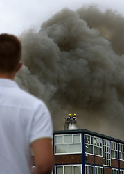 © Licensed to London News Pictures. 01/09/2013. Leyland, UK A man watches as Fire crews put out the fire. The scene at Leyland St Mary's Catholic Technology College in Leyland, Lancashire as it was devastated by the blaze at 4pm yesterday (1st September 2013), which saw 100ft flames - and was tackled by 125 firefighters and 20 engines. Photo credit : Pat Tack/LNP