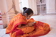 Adu is lost in her mobile phone. In the old days, it was easy to find young girls for Kumari Puja, and families would voluntarily offer a girl for the ritual, which is believed to bring prosperity for the family. However, in modern times, young girls are not enthusiastic and have to be coaxed into sitting for the puja, by promise of gifts. They are too young to understand the rituals or their significance.
