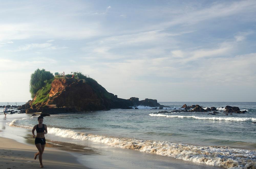 A woman jogging along Mirissa beach, Sri Lanka