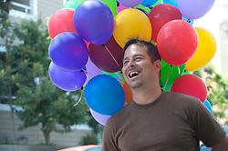 man enjoying himself while holding colorful balloons
