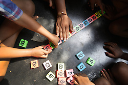 A group of children play a game using local language letter shapes (Oriya) that they try to put in alphabetic order.  KATAKPADA Village is low caste with many people being labourers although some do have greater resources and keep animals.  Prem assists a kindergarten in the village.
