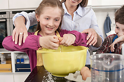 Schoolgirl cracking an egg into a mixing bowl in home economics class, Bavaria, Germany