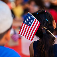 Jasmine Gomez, 8, wears a flag in her hair to show her American pride as she stands in line to get her face painted at the Fourth of July celebration at the McKinley County Courthouse Square in downtown Gallup.