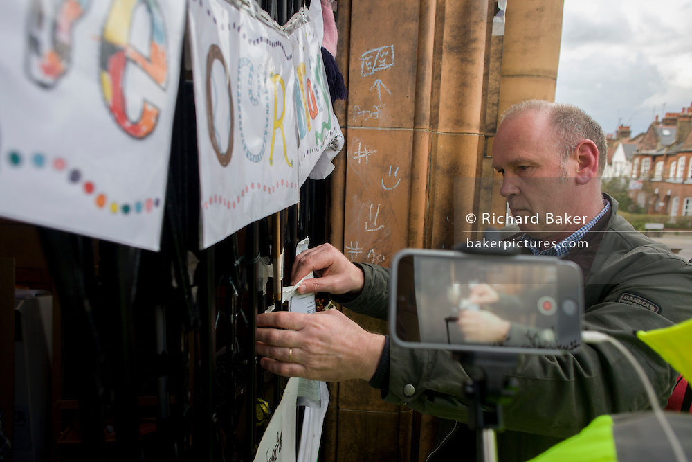 A court official posts an eviction notice to the front gates of Carnegie Library in Herne Hill, south London while occupiers remain inside the premises on day 9 of its occupation, 8th April 2016. The angry local community in the south London borough have occupied their important resource for learning and social hub for the weekend. After a long campaign by locals, Lambeth have gone ahead and closed the library's doors for the last time because they say, cuts to their budget mean millions must be saved.
