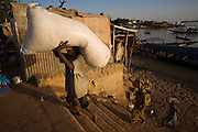 People unloading a boat in Mopti's harbour. At the confluence of the Niger and the Bani rivers, between Timbuktu and Ségou, Mopti is the second largest city in Mali, and the hub for commerce and tourism in this west-african landlocked country.
