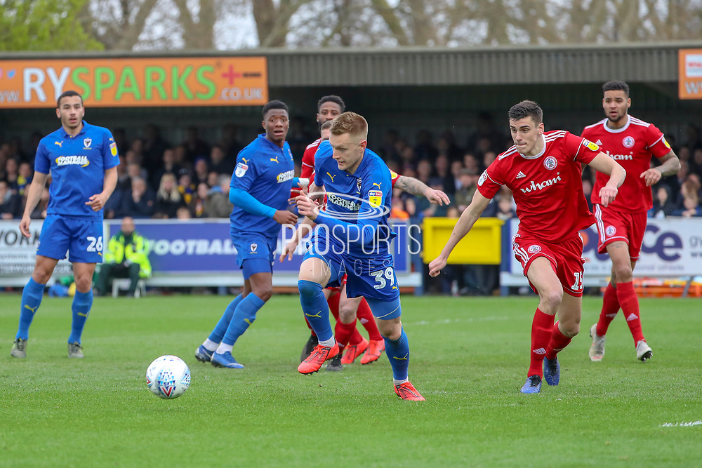 AFC Wimbledon striker Joe Pigott (39) taking on Accrington Stanley defender Ross Sykes (15) during the EFL Sky Bet League 1 match between AFC Wimbledon and Accrington Stanley at the Cherry Red Records Stadium, Kingston, England on 6 April 2019.