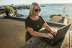United States, Washington, Kirkland, woman on laptop in park. MR
