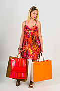 Tired and depressed young blond woman in colourful summer dress out shopping On white Background