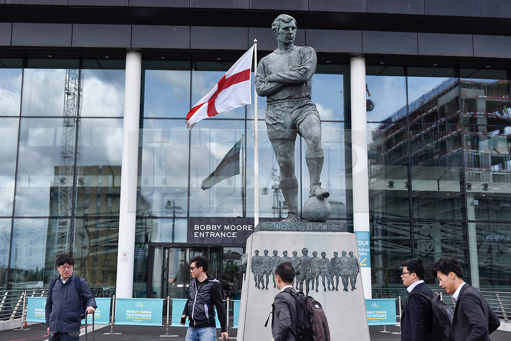 © Licensed to London News Pictures. 26/04/2018. LONDON, UK.  Tourists stand near the statue of Bobby Moore outside Wembley Stadium.  It is reported that the Football Association (FA) has received a bid of GBP800m from Shahid Khan, owner of Fulham FC and the Jacksonville Jaguars NFL franchise, to purchase the stadium.  If the bid is successful, the FA will retain its organisational base at the stadium, but will open the way for the creation of the first NFL franchise located out of the United States.  Photo credit: Stephen Chung/LNP
