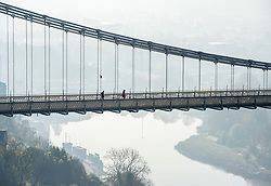 © Licensed to London News Pictures; 05/11/2020; Bristol, UK. Lockdown 2.0 during Covid-19. People walk and take exercise on the Clifton Suspension Bridge on a misty morning of the first day of lockdown 2.0, the second lockdown imposed for England as the Government tries to stop the spread of the covid-19 coronavirus pandemic. From 05 November lockdown restrictions come into force across England with all pubs, bars restaurants and entertainment venues shut as well as all non-essential shops. People have been told to stay at home except for work, education, exercise or essential shopping and each person can only meet one other person from outside their household in an outdoors public space. Households must not mix with others indoors, or in private gardens. Photo credit: Simon Chapman/LNP.