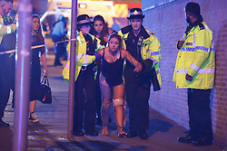 May 22, 2017 - Manchester, England, United Kingdom - An injured concert-goer is helped by police and emergency responders at the Manchester Arena after reports of an explosion. Manchester police reported 'a number of confirmed fatalities and others injured' as hundreds of fans fled the arena. The police suspect terrorism after the deadly explosion that may have been a suicide bombing has killed at least 19 and injured at least 50 people.  (Credit Image: © Joel Goodman/London News Pictures via ZUMA Wire)