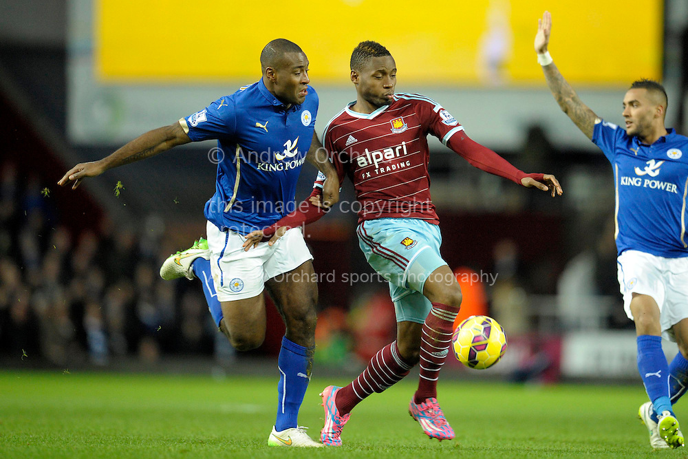 Wes Morgan, the Leicester City captain holds onto Diafra Sakho of West Ham United. Barclays Premier league match, West Ham Utd v Leicester city at the Boleyn ground, Upton Park in London on Sat 20th December 2014.<br /> pic by John Patrick Fletcher, Andrew Orchard sports photography.