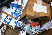 Someone's confidential information and personal data stored on floppy and Zip discs is dumped in a skip (dumpster) on south London street. The digital media may not be readable by modern PC computers but the confidential information may still be taken by those intent on stealing identities for fraudulent purposes. The owner of these discs has nonetheless recklessly tipped them in a now rain soaked box and left them to be seen or taken by passes-by. Lying with building rubbish and household waste, the data is scattered and visible.