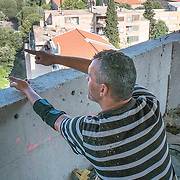 MOSTAR, BOSNIA AND HERZEGOVINA - JUNE 28:  Liubo and ex soldier shows the position and place where snipers would have been hiding during the 1993 war on June 28, 2013 in Mostar, Bosnia and Herzegovina. The Siege of Mostar reached its peak and more cruent time during 1993. Initially, it involved the Croatian Defence Council (HVO) and the 4th Corps of the ARBiH fighting against the Yugoslav People's Army (JNA) later Croats and Muslim Bosnian began to fight amongst each other, it ended with Bosnia and Herzegovina declaring independence from Yugoslavia.  (Photo by Marco Secchi/Getty Images)