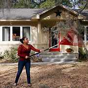 Sofia Hernandez, 23, of Beaufort, uses a rake to pull Spanish moss from a tree while doing yard work at a home off of Newcastle Street in the Pigeon Point neighborhood on February 19, 2014.