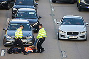 A Surrey Police officer drags an Insulate Britain climate activist from the anticlockwise carriageway of the M25 between Junctions 9 and 10 where she had been protesting as part of a campaign intended to push the UK government to make significant legislative change to start lowering emissions on 21st September 2021 in Ockham, United Kingdom. Both carriageways were briefly blocked before being cleared by Surrey Police. The activists are demanding that the government immediately promises both to fully fund and ensure the insulation of all social housing in Britain by 2025 and to produce within four months a legally binding national plan to fully fund and ensure the full low-energy and low-carbon whole-house retrofit, with no externalised costs, of all homes in Britain by 2030.