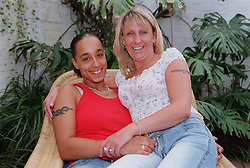 Lesbian couple sitting together on wicker chair hugging,
