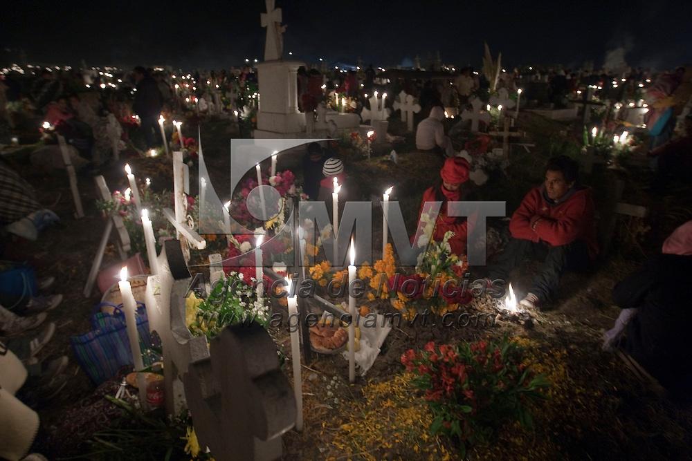 Toluca, Méx.- Miles de personas, siguiendo la tradicion ancestral del dia de muertos, velan a sus difuntos al pie de las tumbas que adornan con flores y alumbran con velas en el panteon de la comunidad Otomí de San Pablo Autocpan, a 8 kilometros al norte de la ciudad de Toluca. Agencia MVT / José Hernández. (DIGITAL)