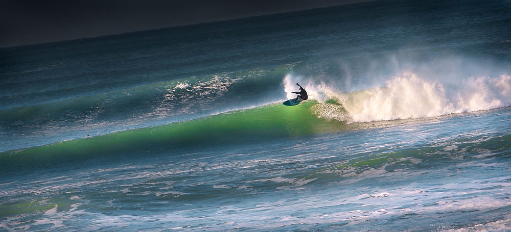 Surfer catching a wave in winter at Secrets surf spot, St Ouen's Bay, Jersey, Channel Islands